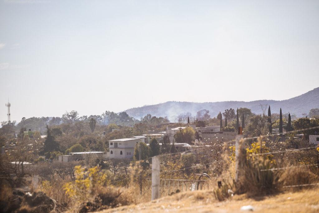 Rauch zwischen Häusern und Feldern