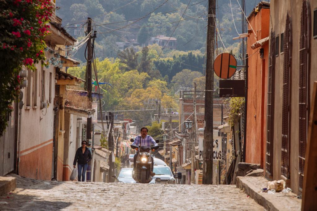 Rollerfahrer und hügelige Straße in Tepoztlán