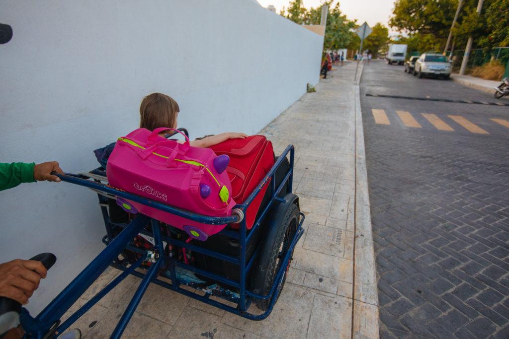 Kind auf Koffern auf Lastenrad auf Isla Mujeres