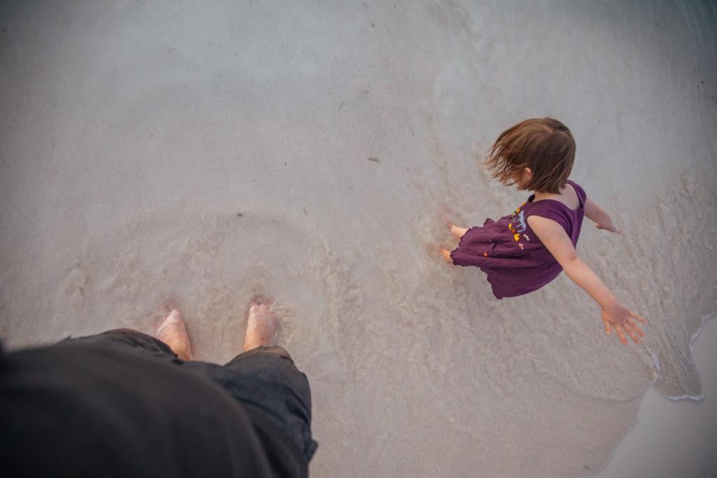 Tochter springt in der Brandung an der Playa Norte herum