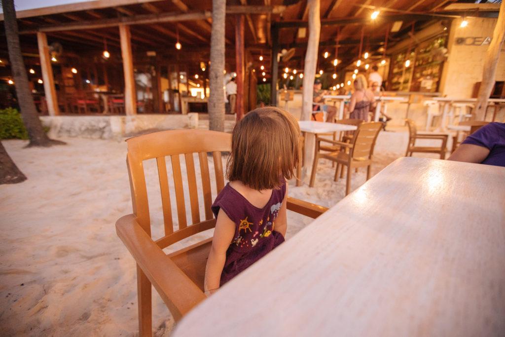 Tochter am Tisch an Strand, Oceanvs Club