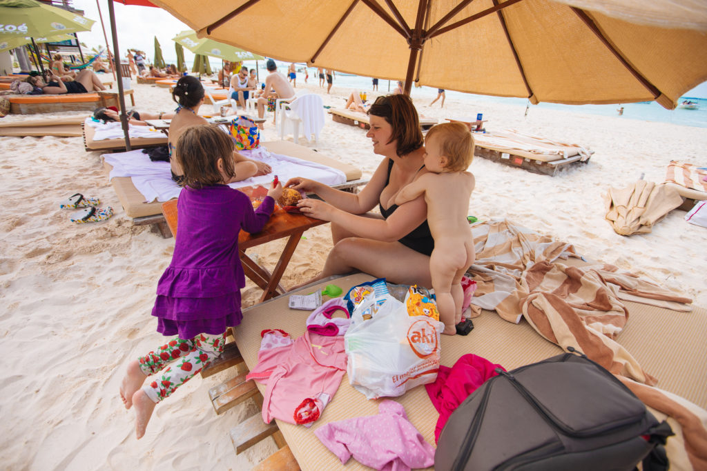 Frau und Kinder verzehren Geburtstagskuchen am Strand