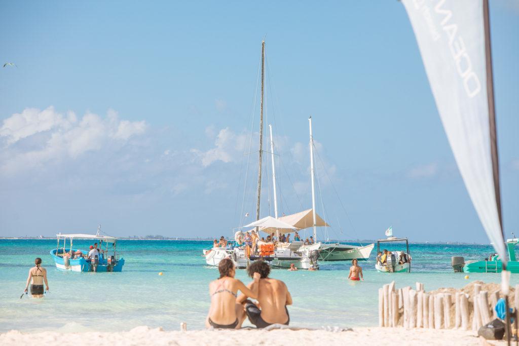 Pärchen vor Booten, Badenden und karibischem Meer
