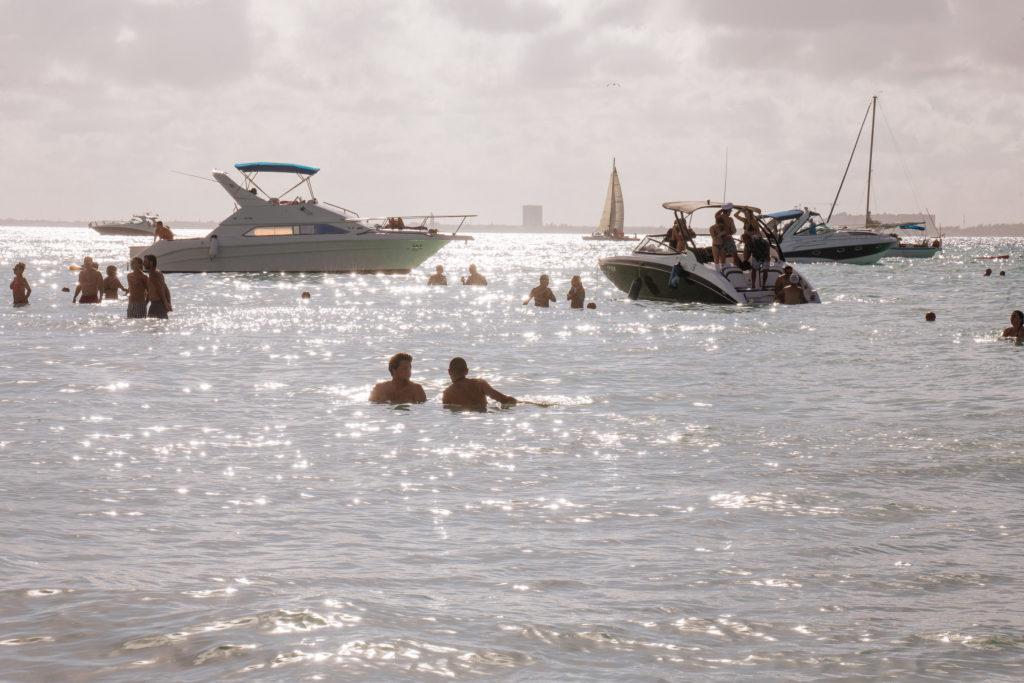 Glitzerndes Wasser, Badende und Boote