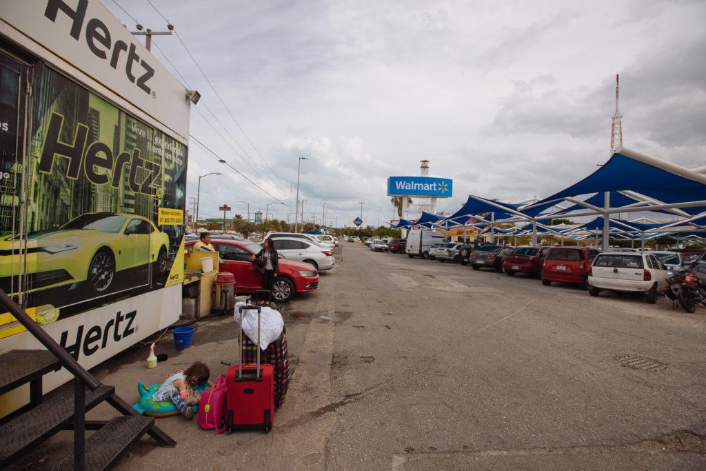 Tochter und Koffer an der Hertz-Zentrale des Walmart-Parkplatz Cancun