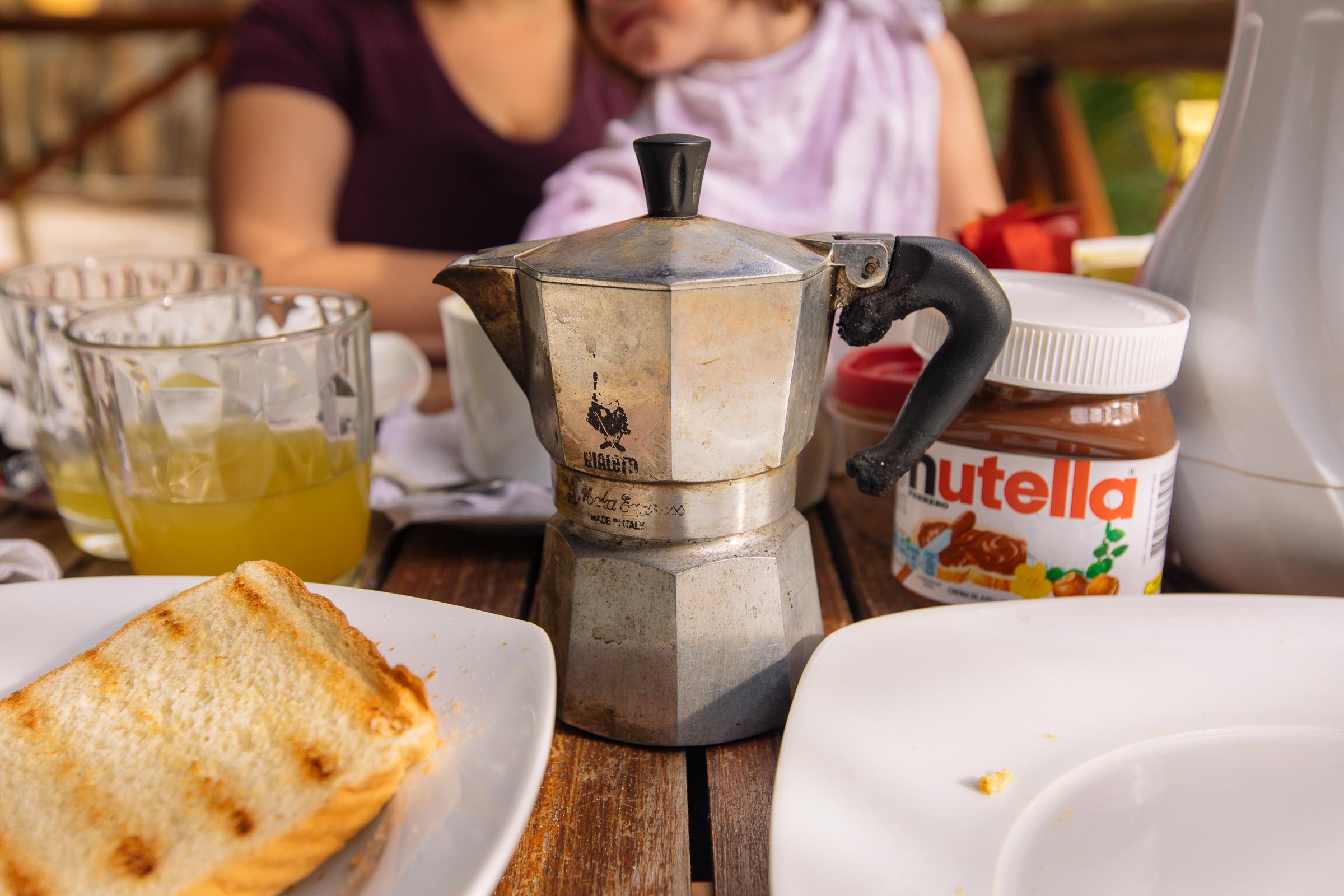Toast, Saft, Espressokanne, Nutella auf dem Frühstückstisch
