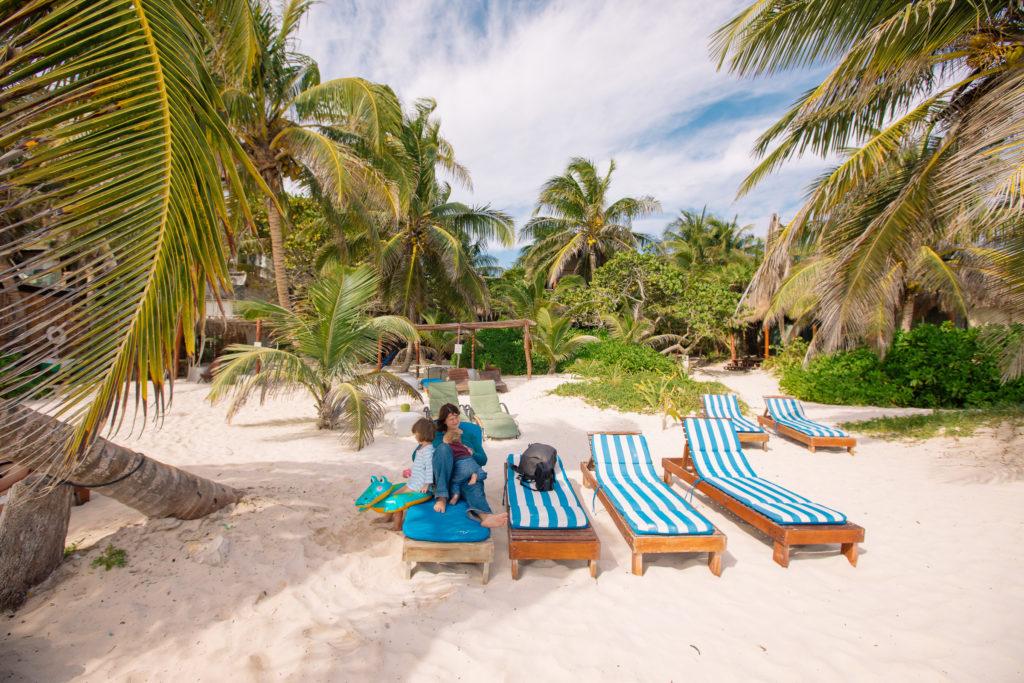 Frau und Kinder auf den Strandliegen der Playa Xcanan