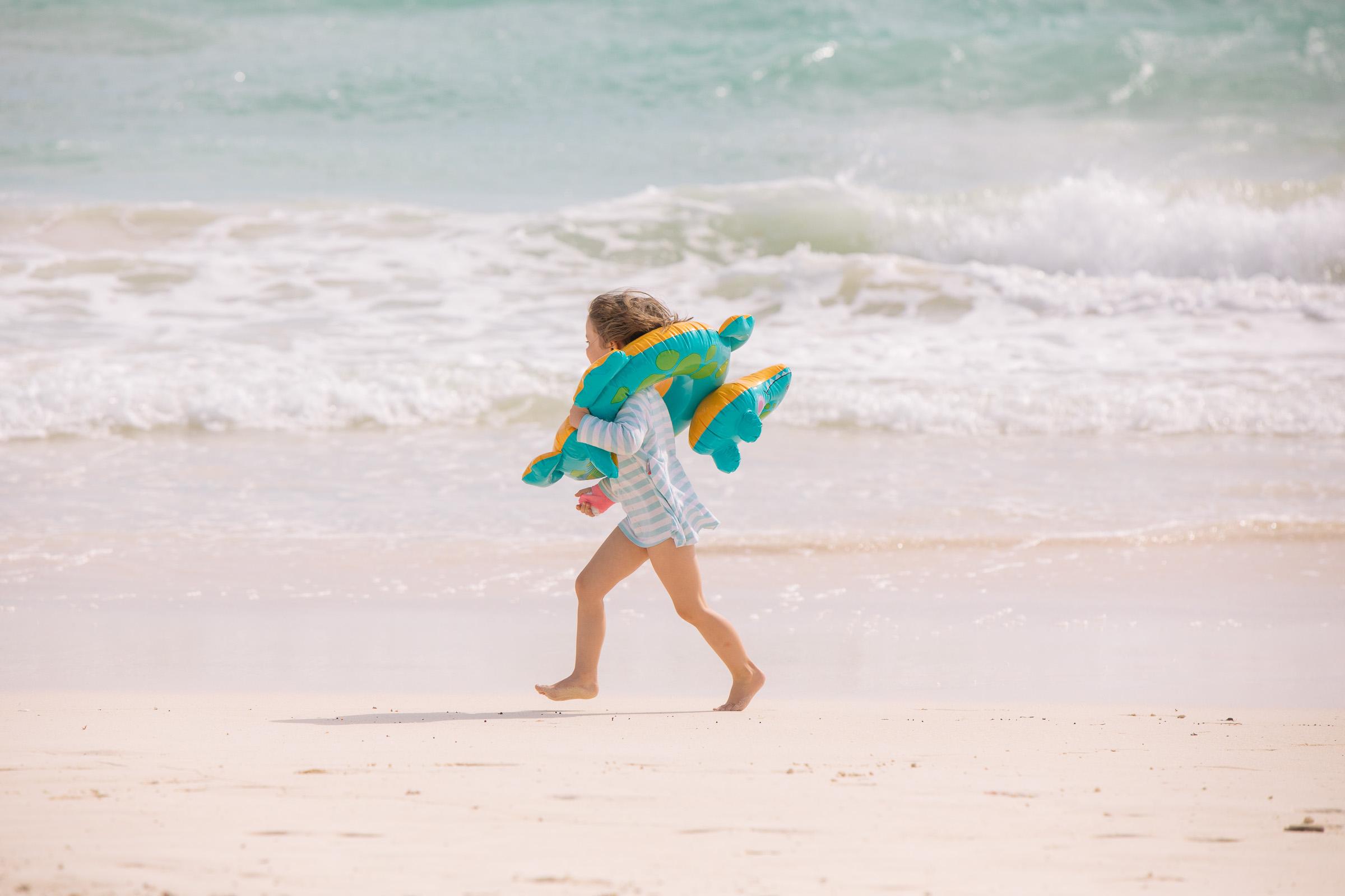 Töchterlein rennt mit Badetier vor dem Meer