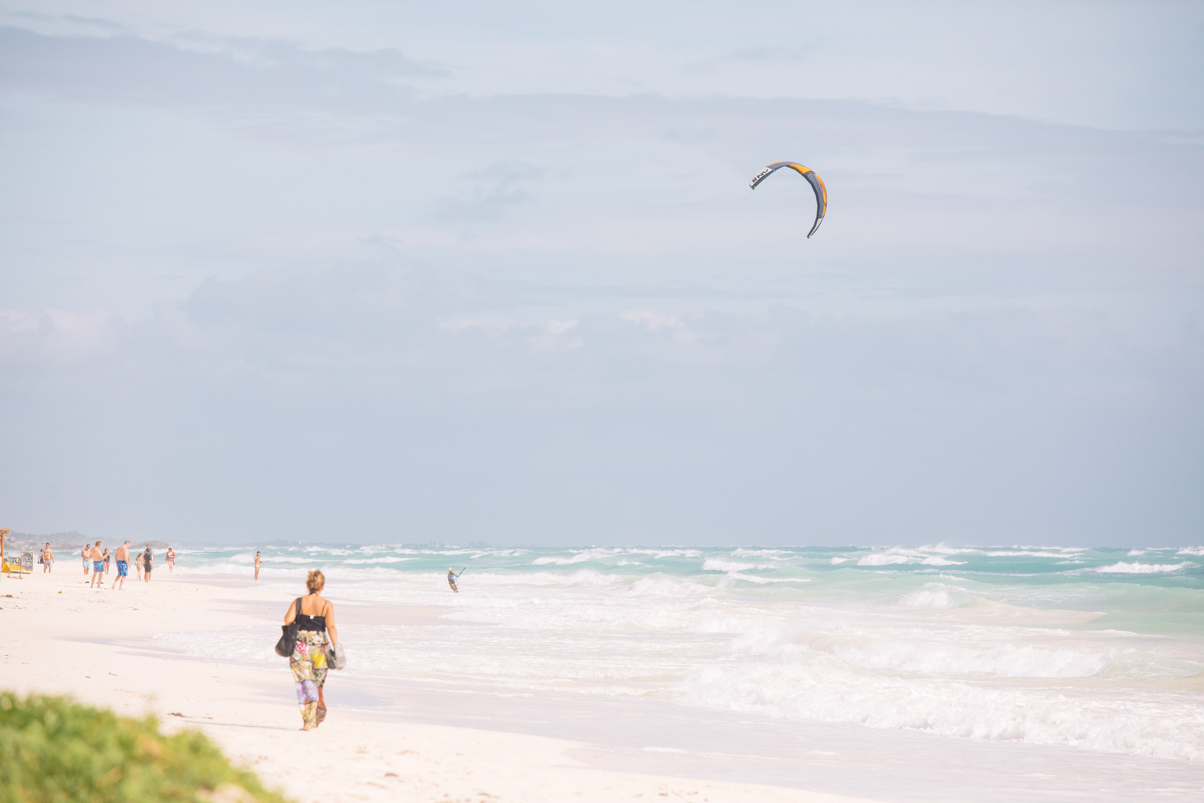 Kitesurfer und wandernde Frau in Tulum