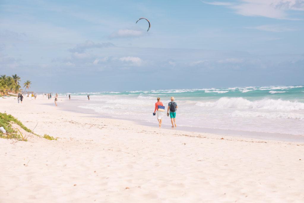 Spaziergänger und Kitesurfer am Strand von Tulum