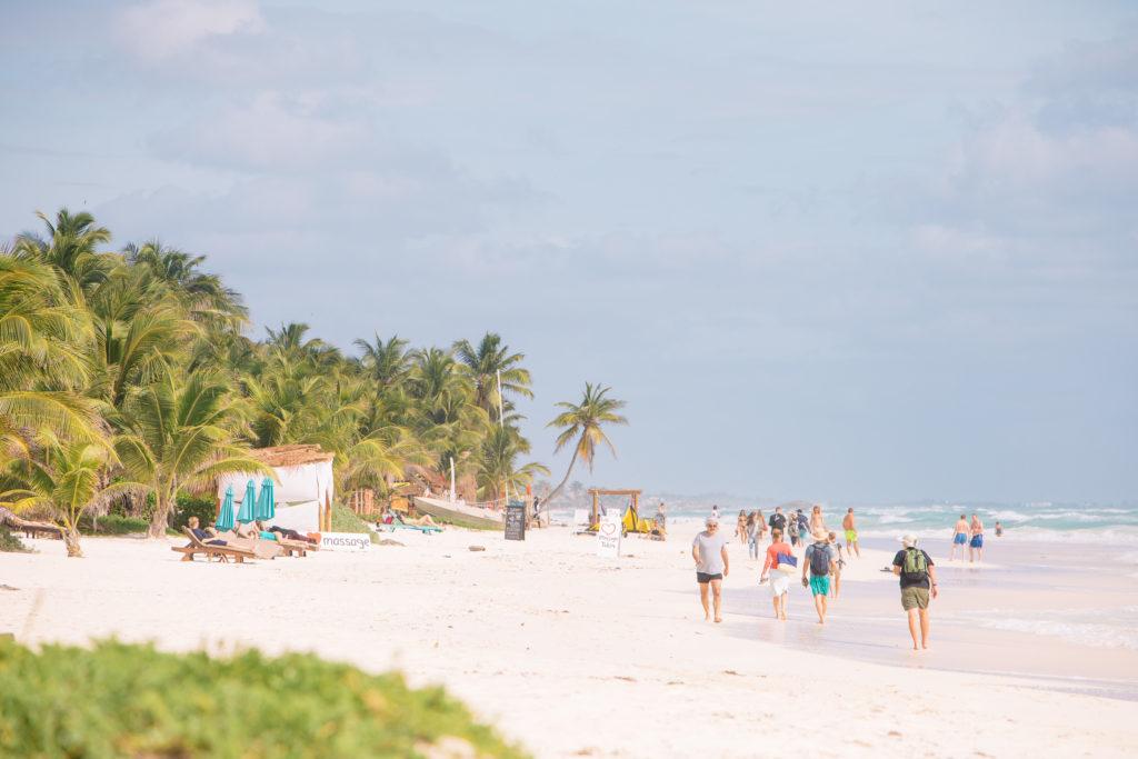 Palmen, Strand, Meer und Spaziergänger in Tulum