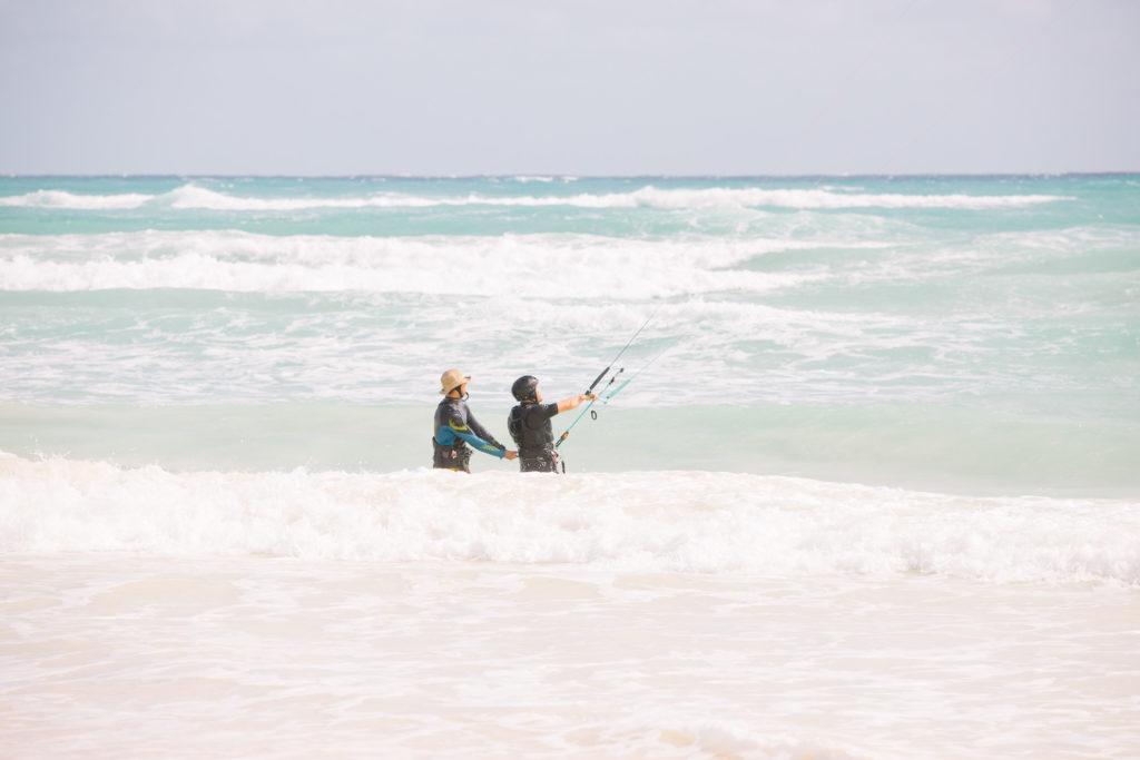 Kitesurflehrer und Schüler in den Wellen