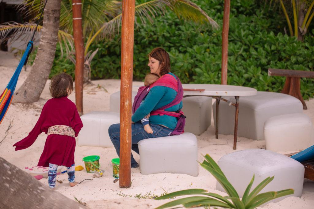 Töchterlein mit Myriams Pullover und Sohn in der Trage am Strand