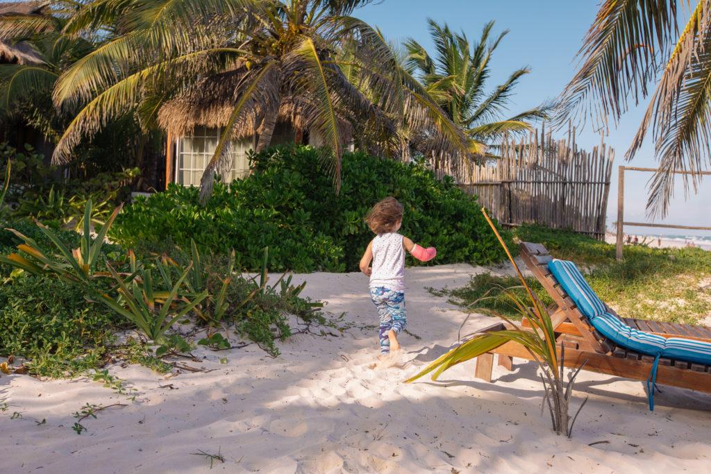 Tochter rennt mit dem Gips vom Strand zwischen die Palmen