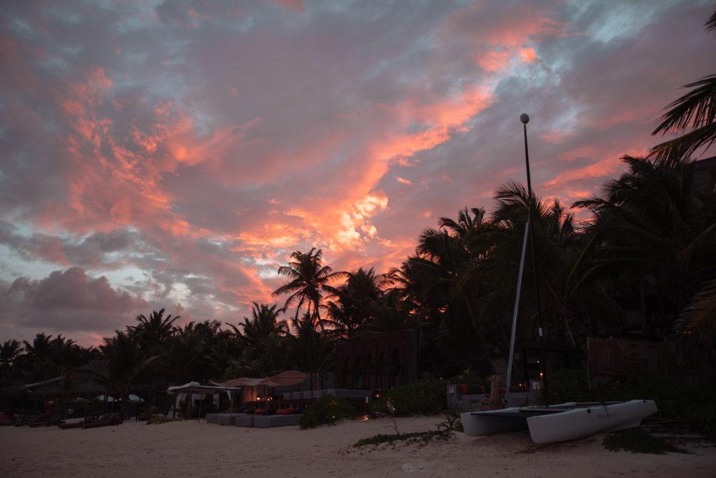 Feurige Abendwolken über den Palmen in Tulum