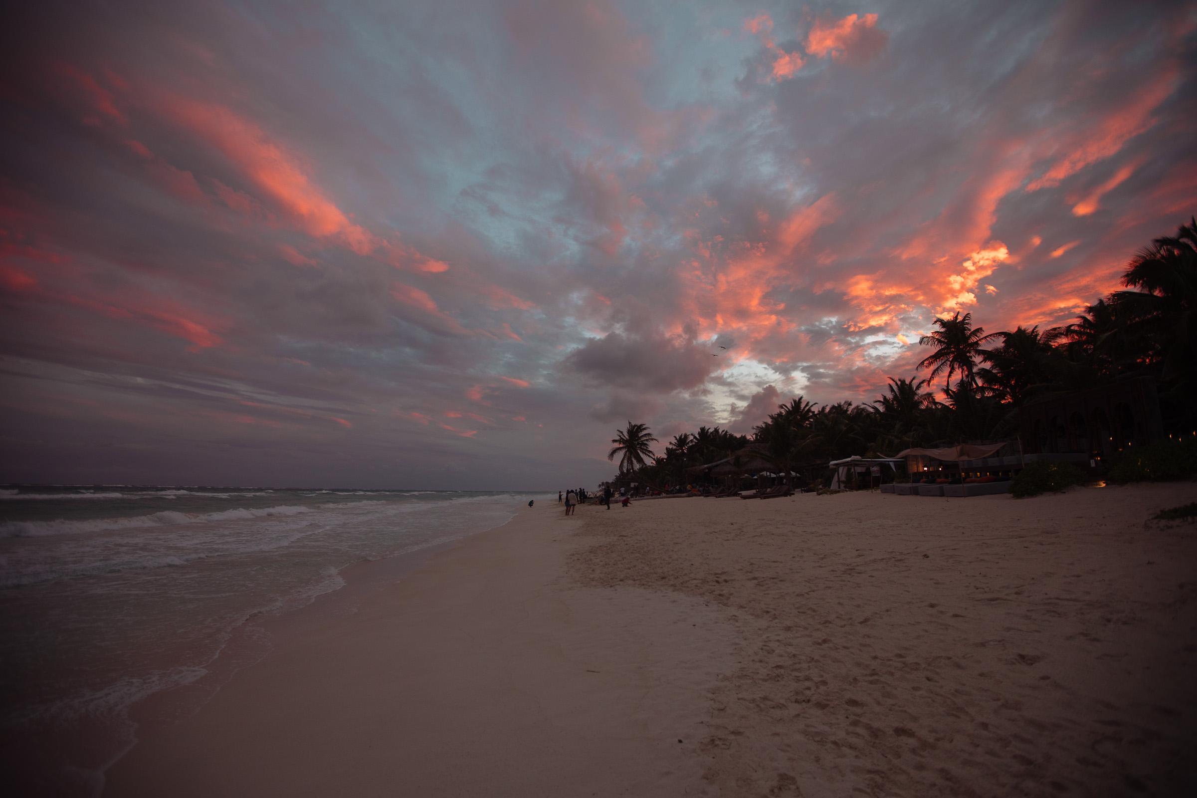 Meer, Brandung, Strand, Palmen und Feuerwolken im Sonnenuntergang
