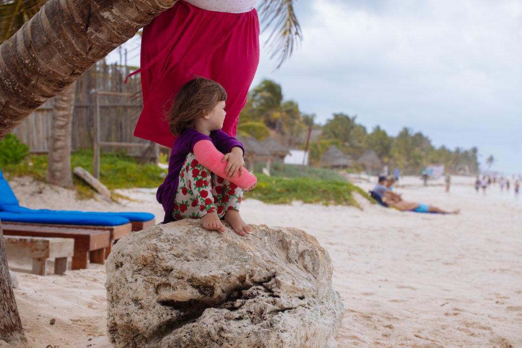 Töchterlein mit rosa Gips unter der schiefen Palme der Playa Xcanan