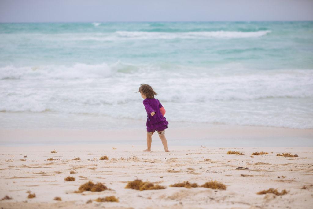 Töchterlein flitzt im Kleid am Wasser entlang
