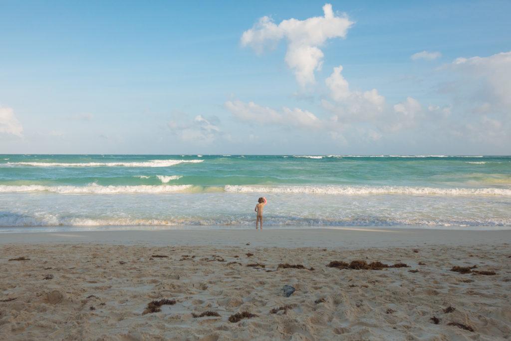 Tochter hält ihren Gips vorm karibischen Meer nach oben