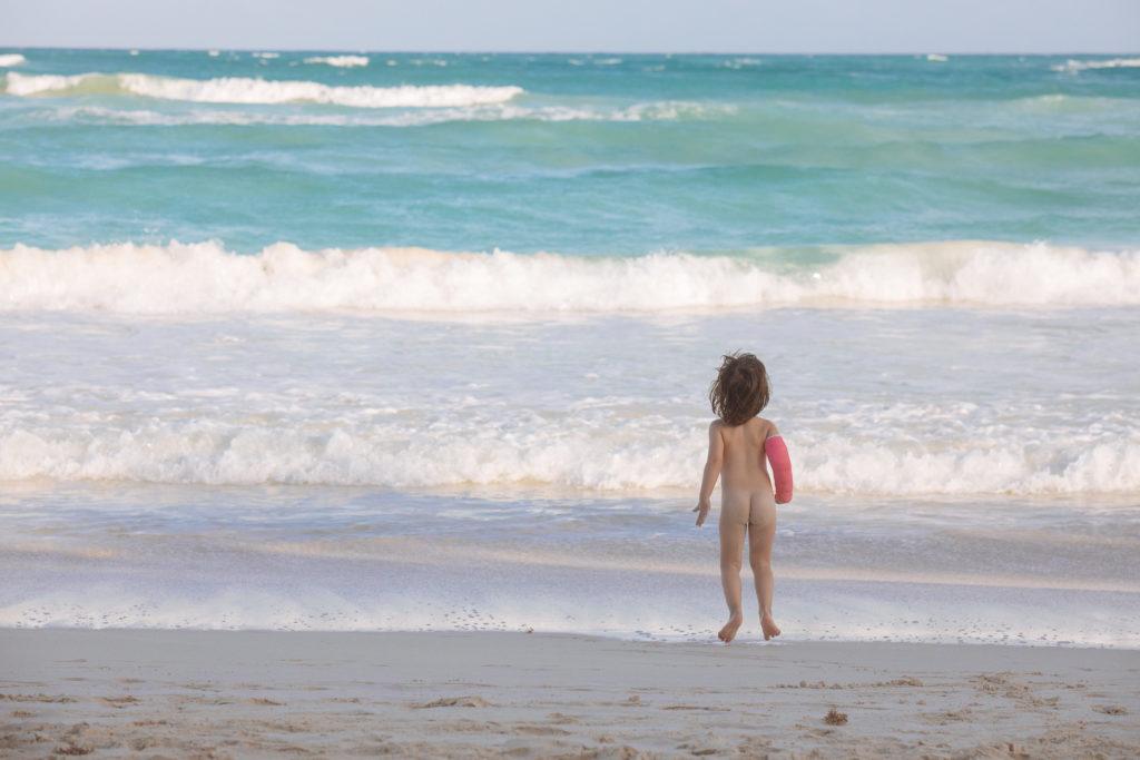 Töchterlein hopst nackig mit Gips vorm karibischen Meer