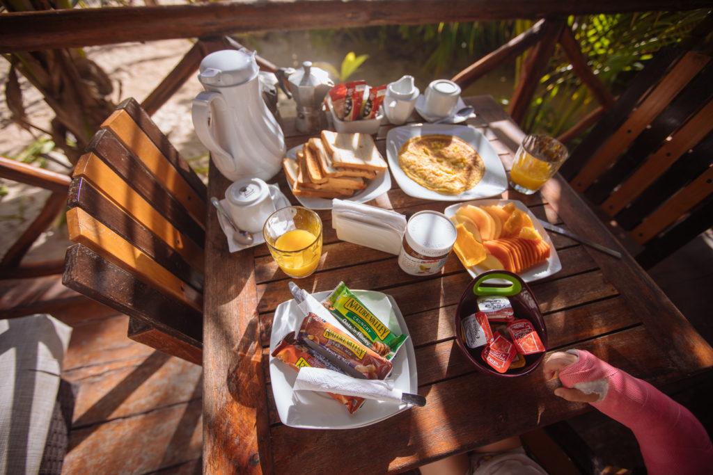 Toast, Müsliriegel, Eierkuchen, Mango, Papaya und Nutella auf dem Frühstückstisch