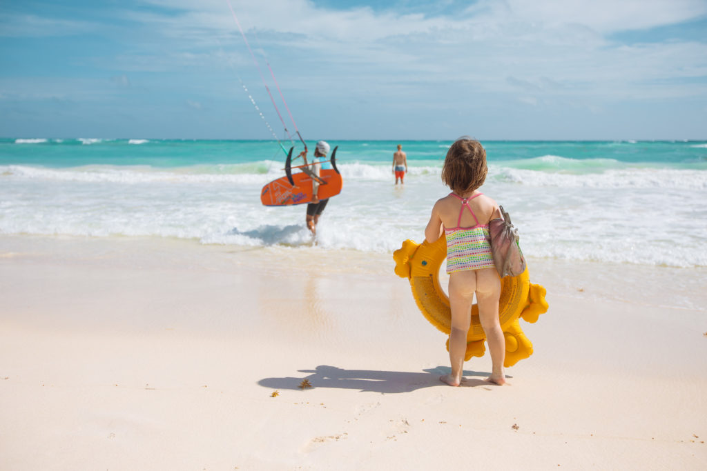 Töchterlein mit Planschkrokodil guckt einem Kitesurfer zu