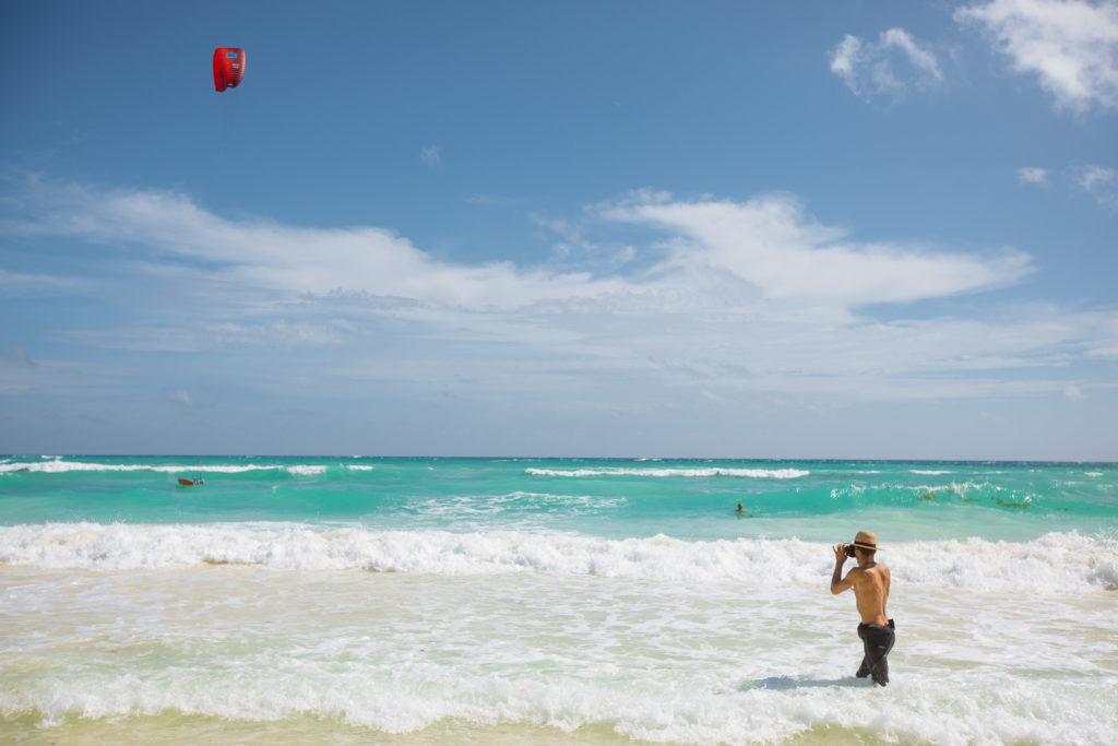 Kitelehrer fotografiert Kitesurfer im Meer