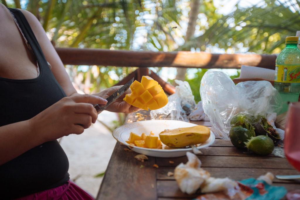 Frau am Mango schneiden auf der Terrasse