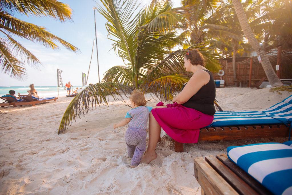 Frau und Sohn in der Abendsonne auf der Strandliege vor einer kleinen Palme