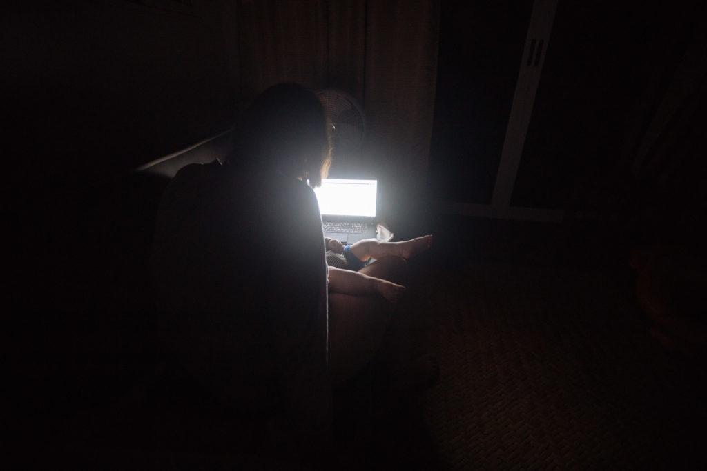 Frau besorgt im Dunkeln Boardingpässe mit Sohn auf dem Schoß