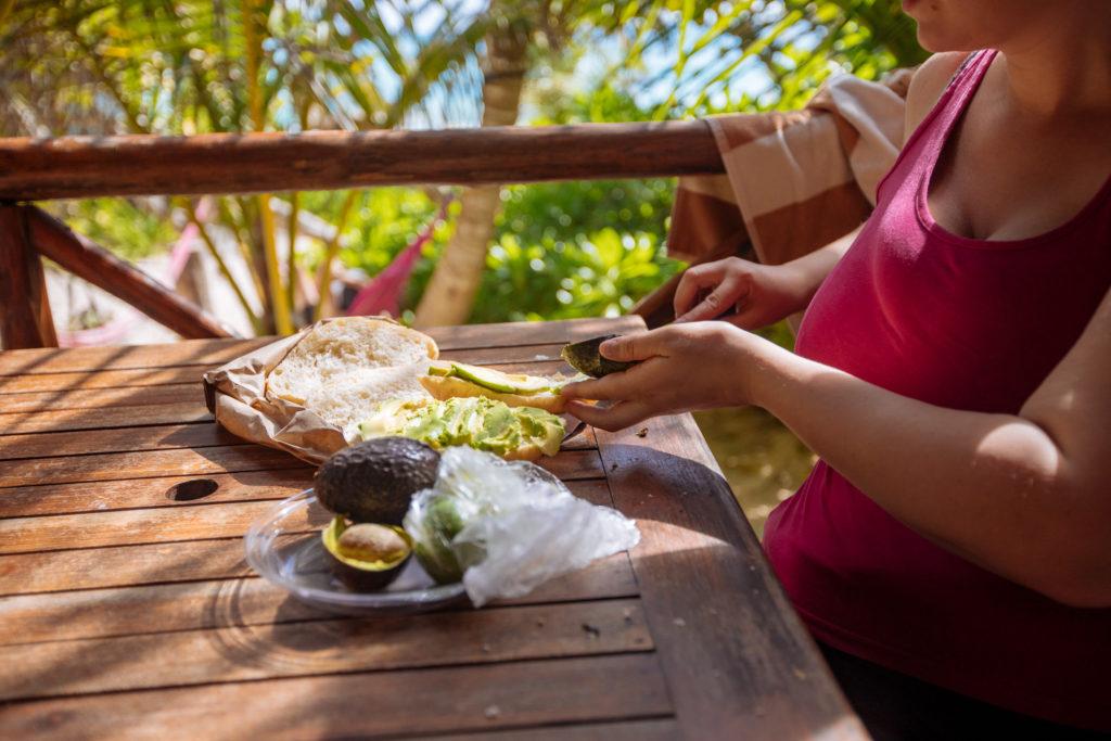 Frau schnippelt Avocado auf der Terrasse in der Karibik am Tag der Abreise