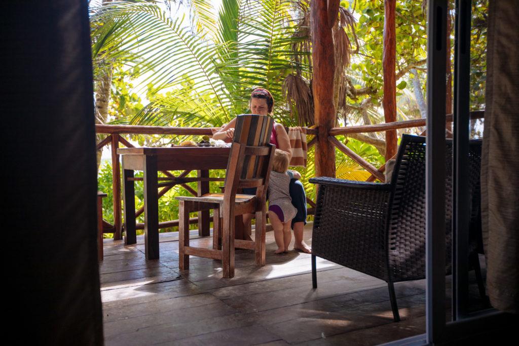 Sohnemann guckt Frau beim Schnippeln auf der Veranda in der Karibik zu