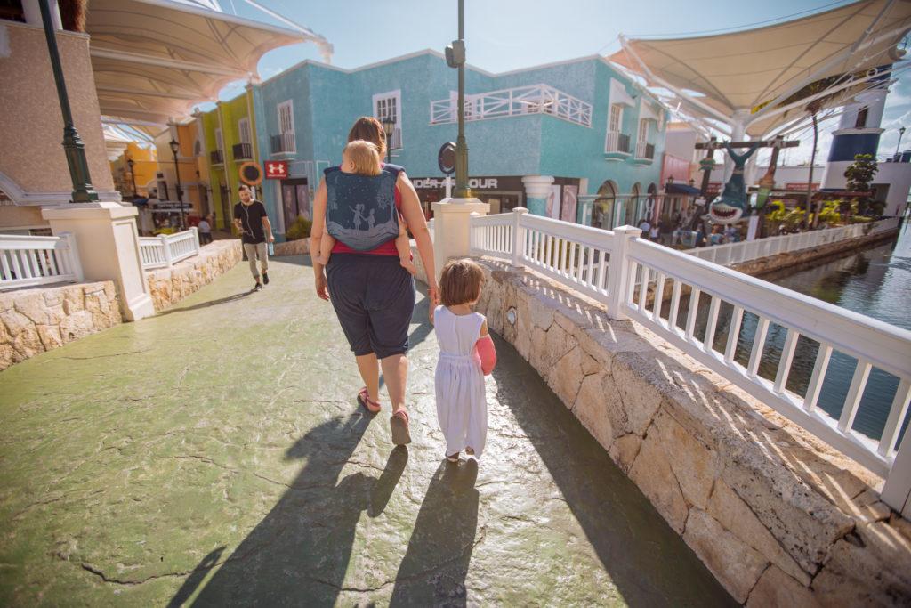 Frau und Kinder betreten Shoppingcenter La Isla in Cancun