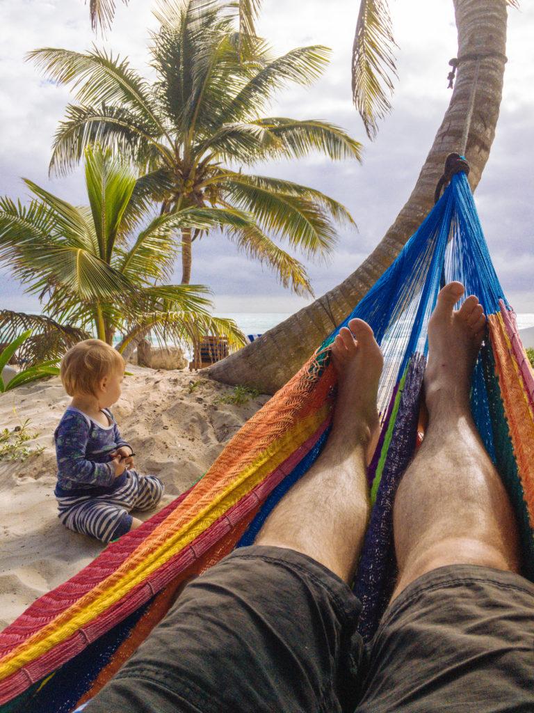 Hängematte mit Füßen zwischen Palmen und der Sohnemann