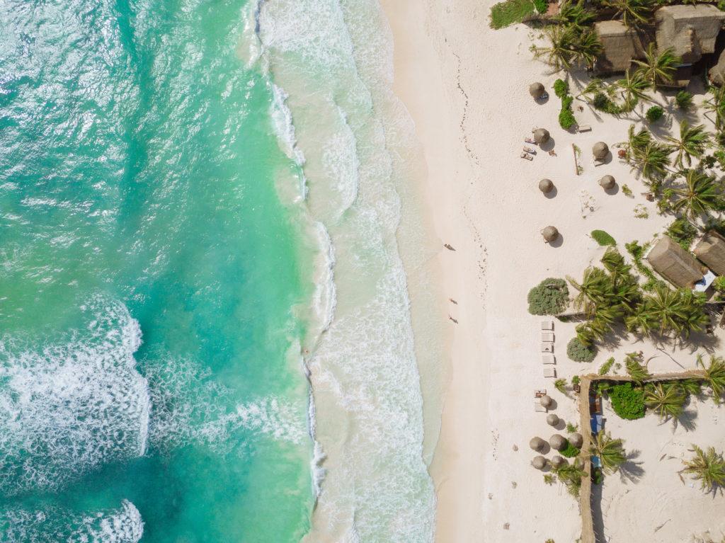 Karibisches Meer und Sonnenschirme von oben