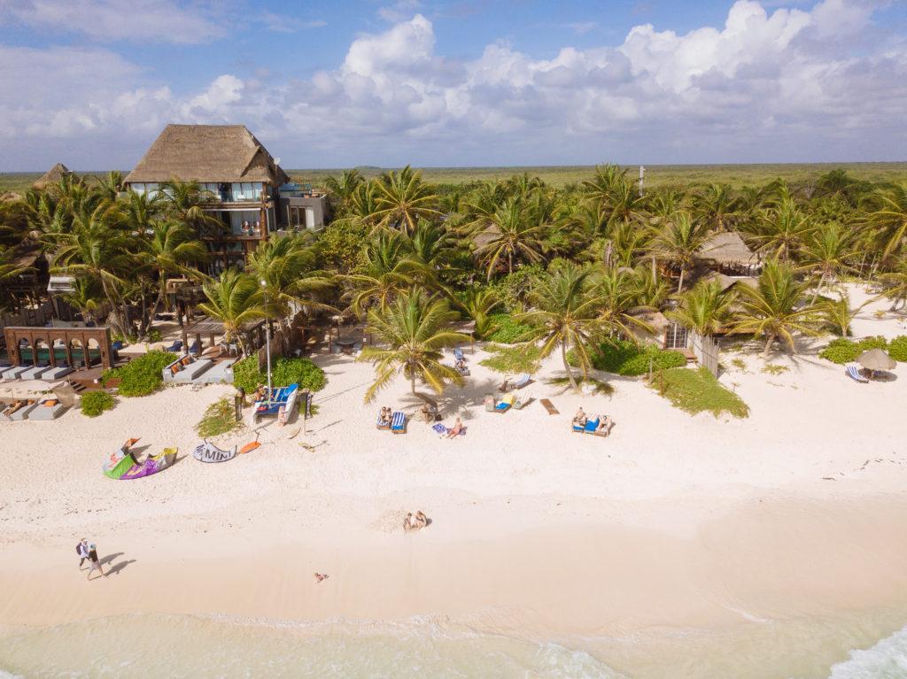 Tulum Playa bei der Playa Xcanan, Frau und Tochter bauen Sandburg während der Sohn ins Wasser krabbelt