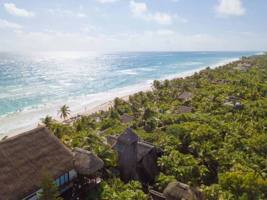 Cabañadächer zwischen Palmen und glitzerndes, blaues Wasser in Tulum playa