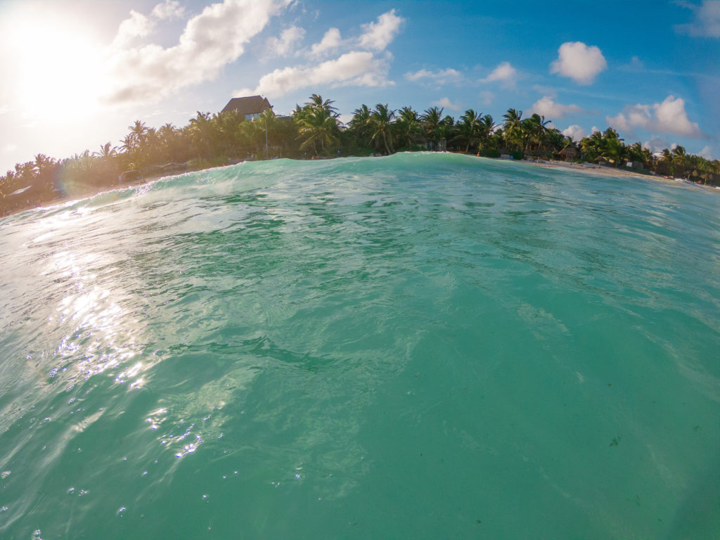 Blick aus dem Wasser vor Playa Xcanan in Tulum mit einer Welle davor