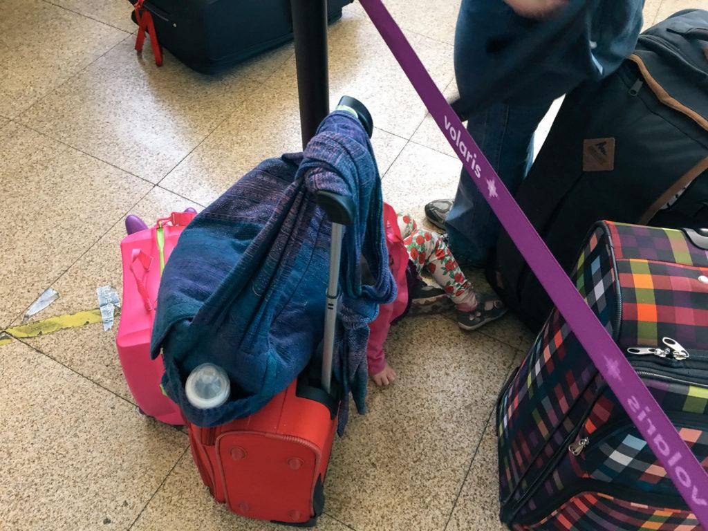 Koffer und Töchterlein in der Warteschlange am Flughafen