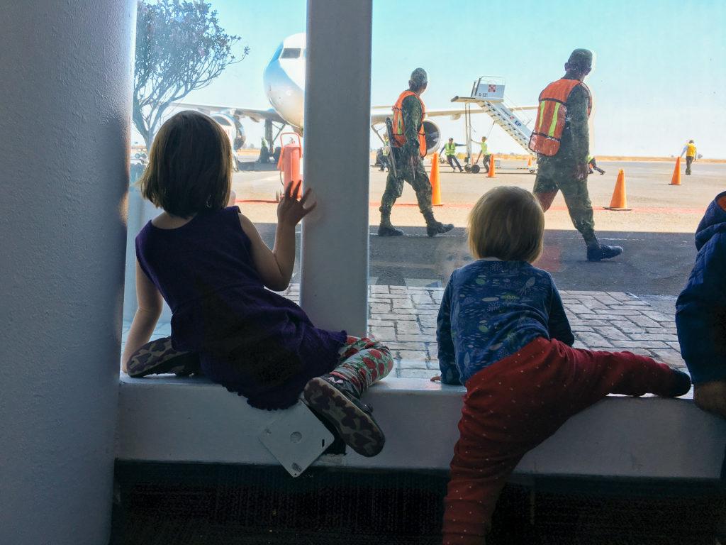 Kinder gucken den Volarisflieger an am Flughafen Puebla