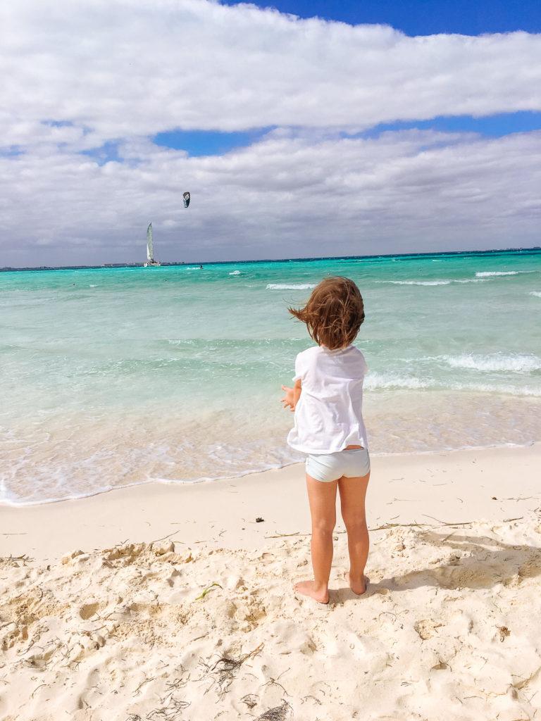 Tochter steht im Wind vorm Meer