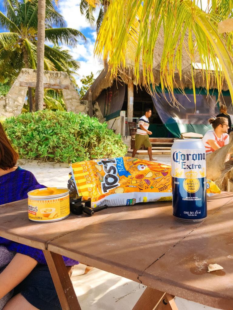 Chips, Dip und Bier am Strand auf dem Tischchen