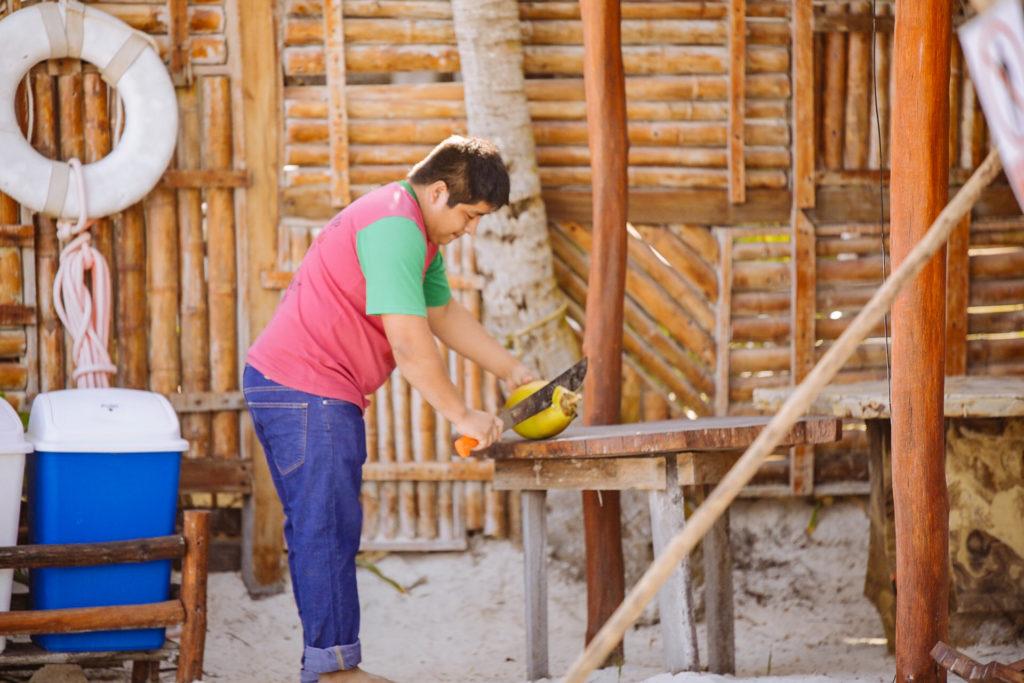 Mitarbeiter Fabios schlachtet eine Kokosnuss mit der Machete